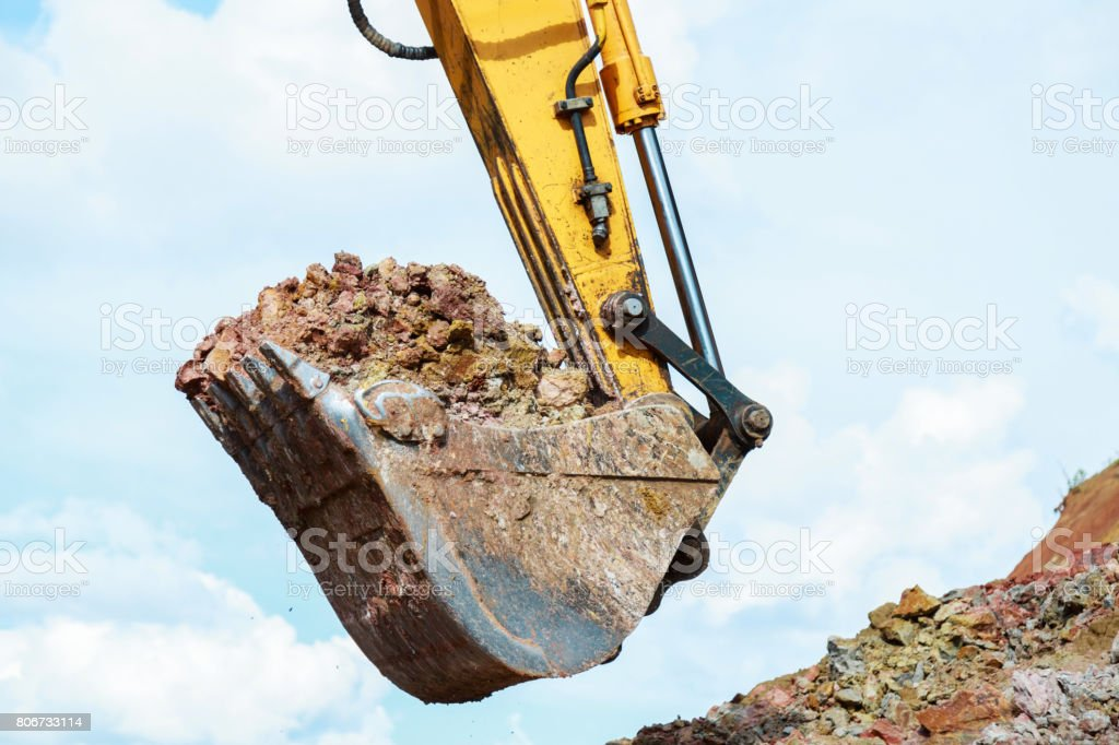 Excavator bucket with ground closeup. Construction work. stock photo