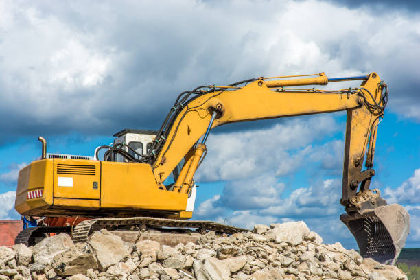 Excavator clears debris Excavator removes the rubble of a torn house demolishing stock pictures, royalty-free photos & images