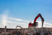 Excavator demolition hammer in progress of demolition an old building