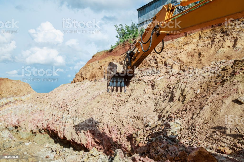 Excavator digging a hole. Work on the construction site. stock photo