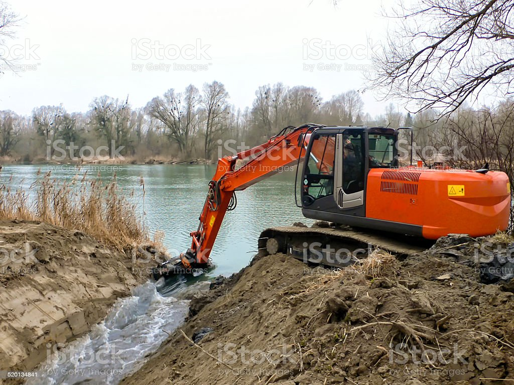 excavator digs inflow into lake for a fish pass stock photo