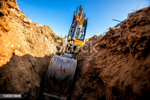 Mini Excavator. Excavator digs the foundation for the house.