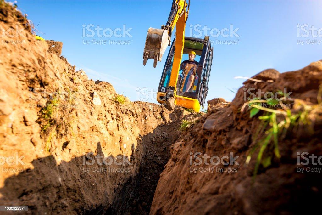 Bagger gräbt den Grundstein für das Haus – Foto