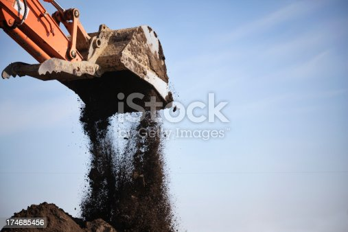Earth mover pouring dirt onto pile. For similar images check out the lightbox...