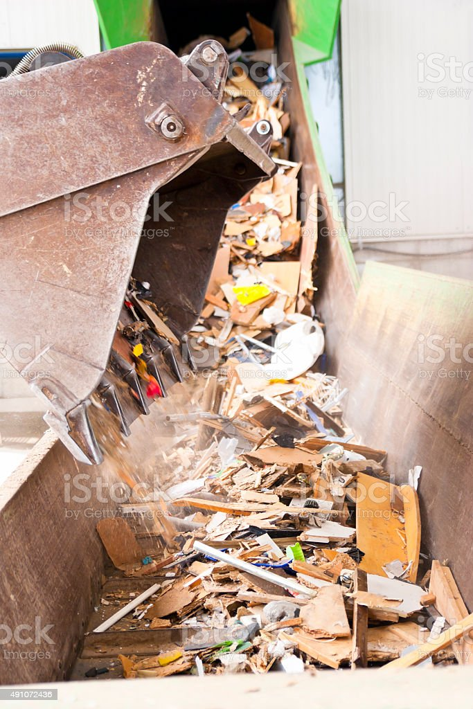 Excavator fills trash on a conveyor belt stock photo