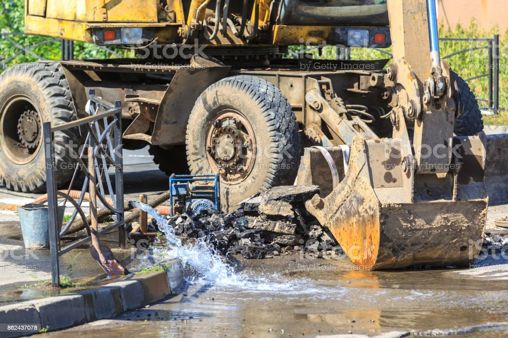 Excavator helps to eliminate the problem of breaking a pipe in the street on a hot summer day stock photo