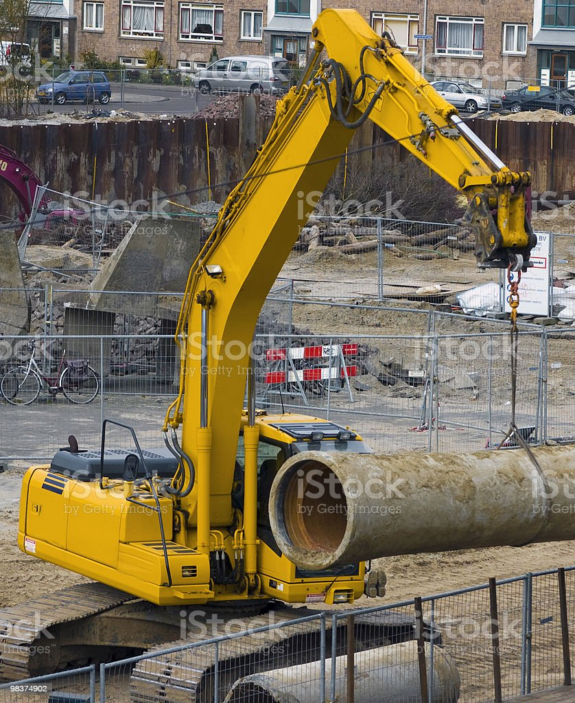Excavator hoisting a sewer-pipe royalty-free stock photo