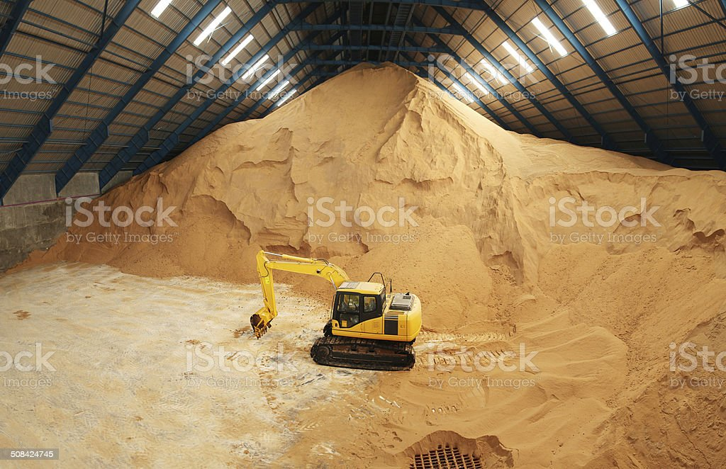 Excavator in a raw sugar storage stock photo