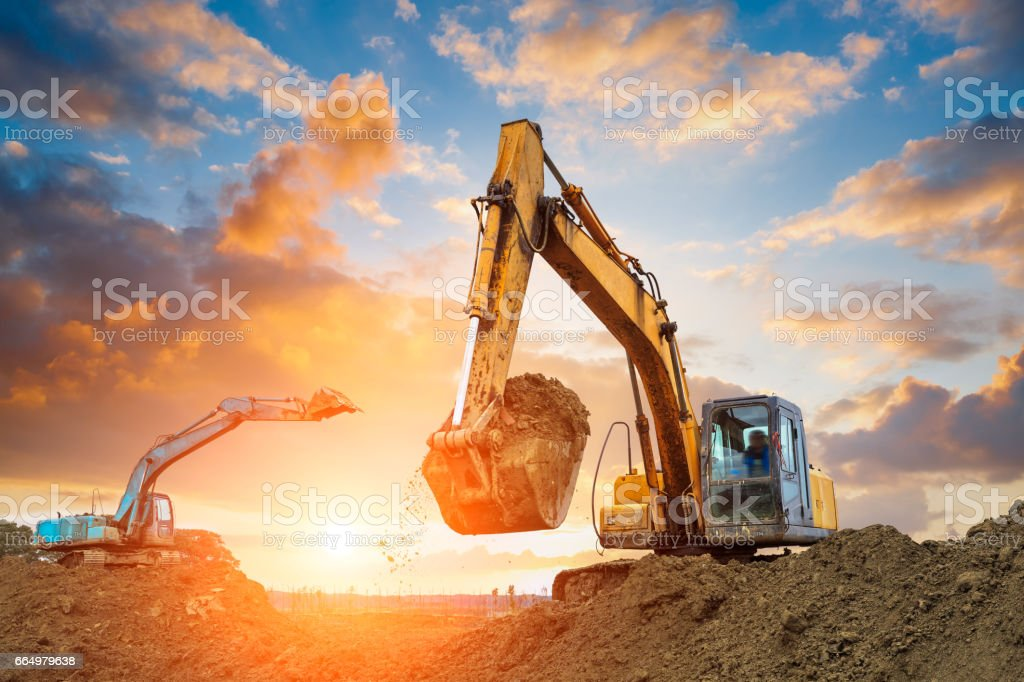 excavator in construction site on sunset sky excavator in construction site on sunset sky background Agricultural Machinery Stock Photo