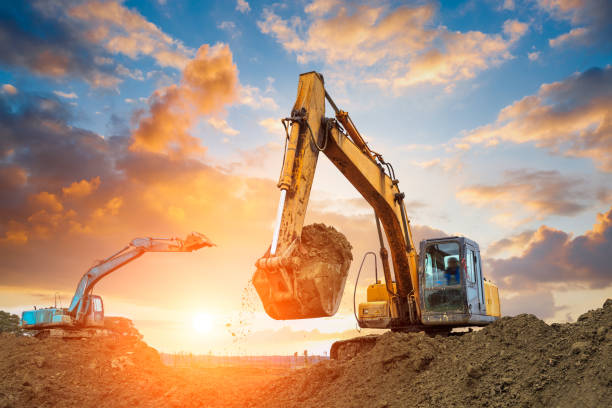 excavator in construction site on sunset sky excavator in construction site on sunset sky background construction machinery stock pictures, royalty-free photos & images