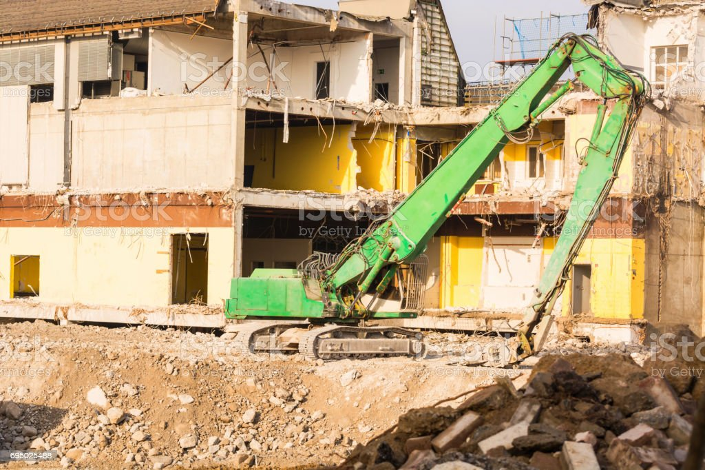 Excavator in front of a demolition site stock photo