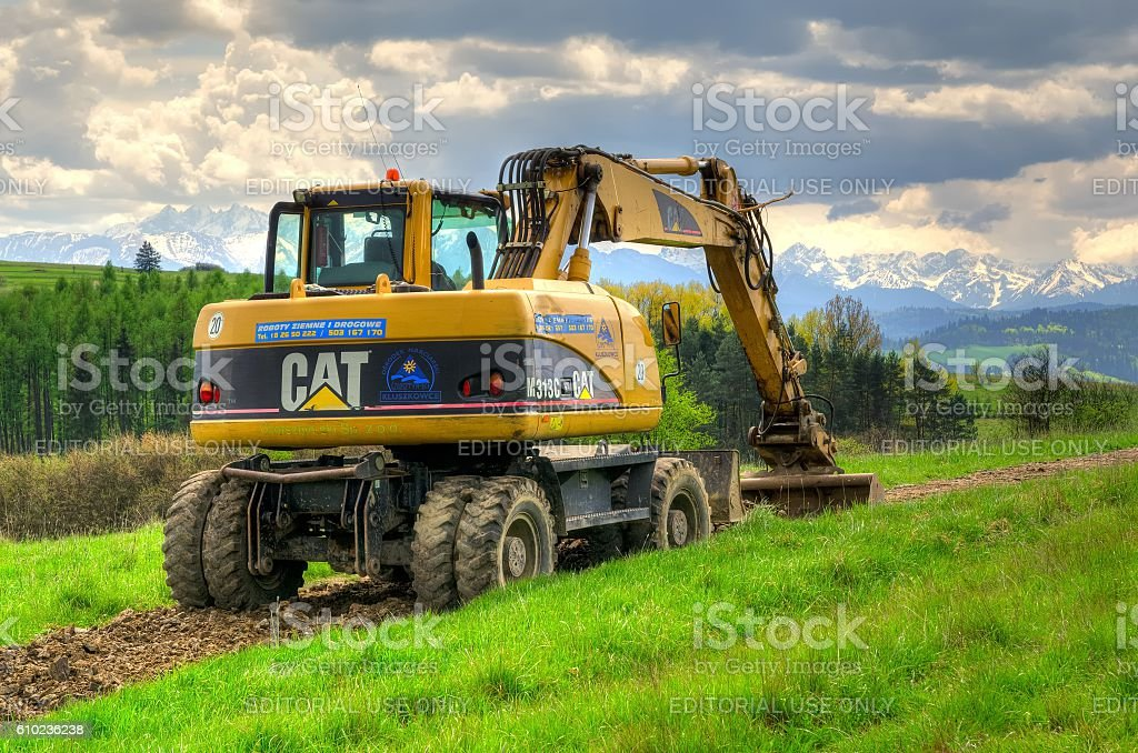 Excavator in the area. Pieniny Mountains, Poland - May 11, 2016: Caterpillar excavator in the area with mountain landscape in background. Agricultural Machinery Stock Photo
