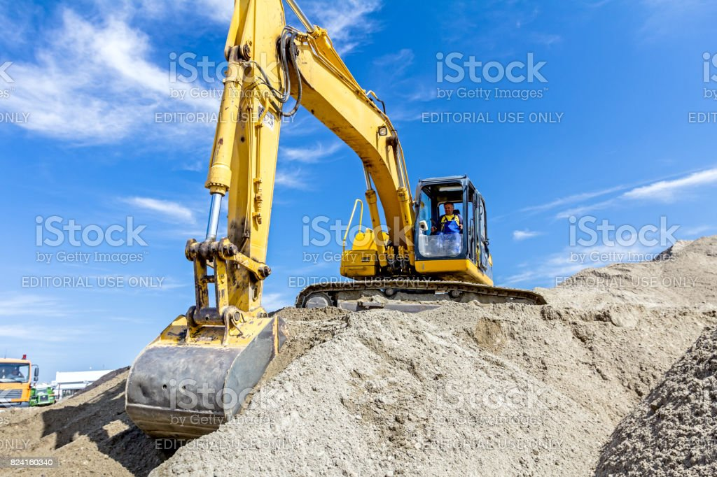 Excavator is preparing pile of sand for loading in truck on building site stock photo