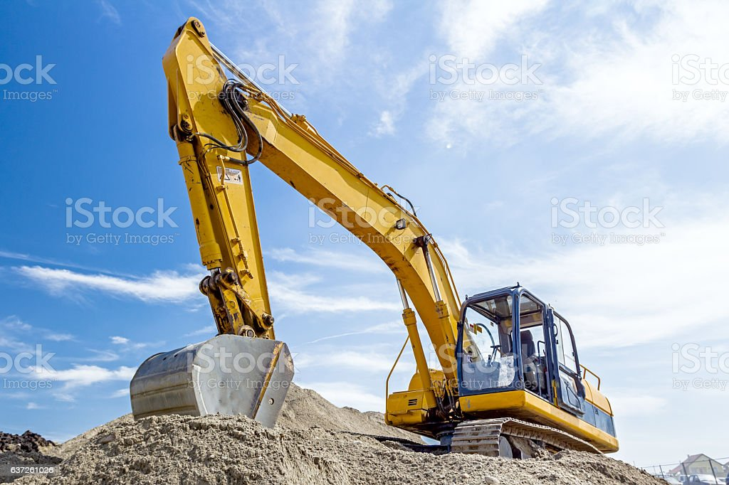 Excavator is preparing pile of sand for loading in truck. stock photo