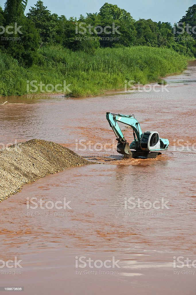 Excavator loader at river with raised bucket royalty-free stock photo