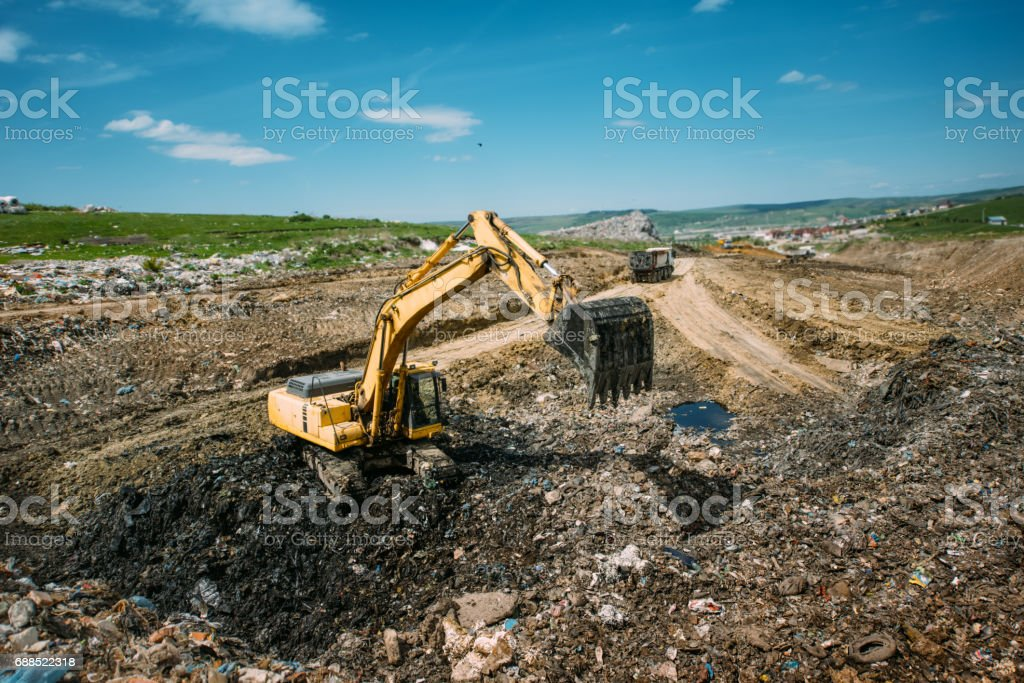Excavator loader, bulldozer working in garbage dump. Recycling and resolving environmental issues stock photo