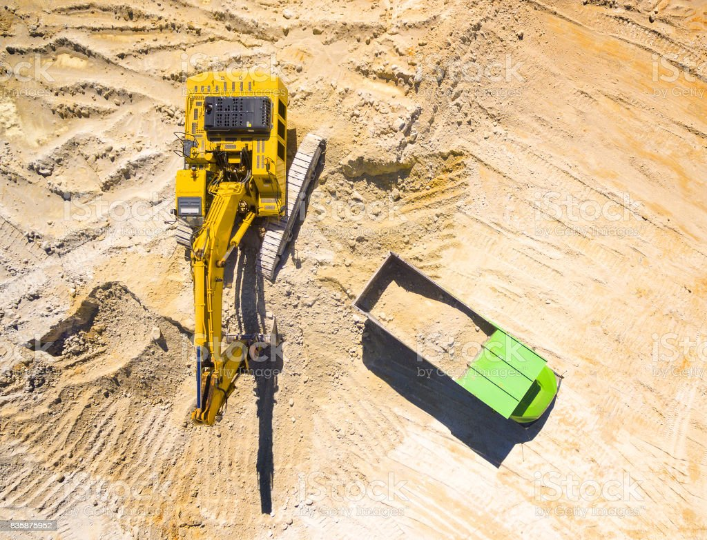 Excavator loading a truck in the mine or on construction site. stock photo
