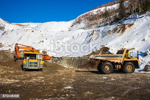 istock Excavator loading dump truck 870448458