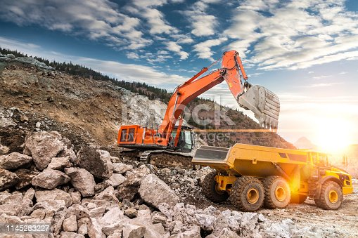Excavator loading dumper truck on mining site