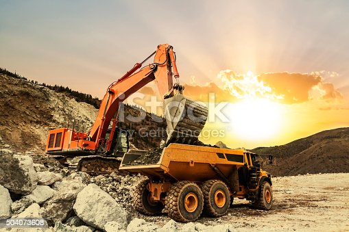 Excavator loading dumper truck on mining site at sunset.