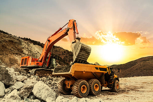 Excavator loading dumper truck on mining site Excavator loading dumper truck on mining site at sunset. construction machinery stock pictures, royalty-free photos & images