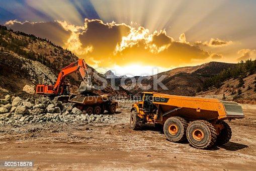 Excavator loading dumper trucks at sunset at mining site.