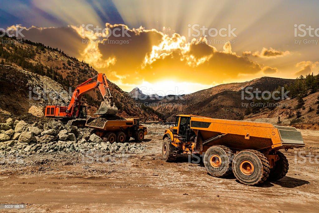 Excavator loading dumper trucks at sunset stock photo