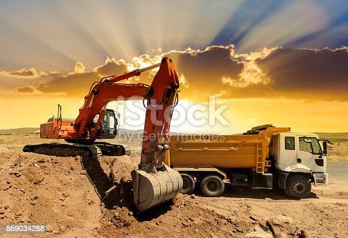 Excavator loading dumper trucks at sunset