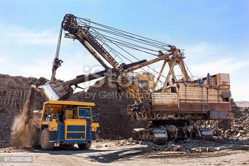 istock Excavator loading yellow dump truck 912569166