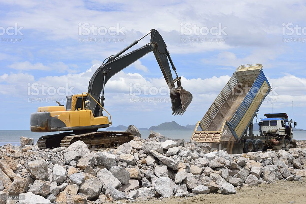 Excavator machine with raised bucket and truck royalty-free stock photo