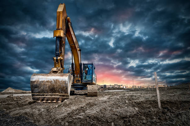 Excavator machinery at construction site Excavator machinery at construction site, sunset in background. construction machinery stock pictures, royalty-free photos & images