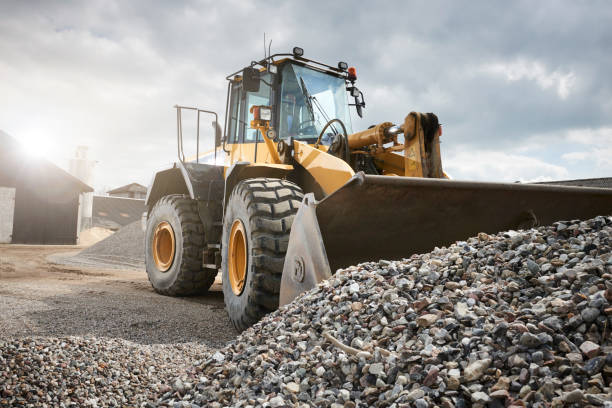 Excavator moving sand in a gravel pit stock photo