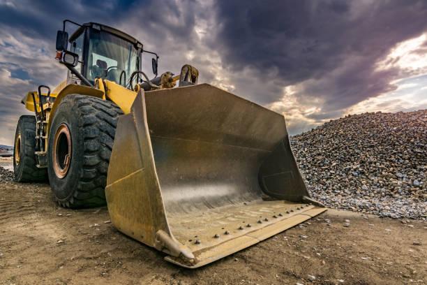 graafmachine verplaatsen van steen en rots in de bouw werkt van een weg - graven stockfoto's en -beelden