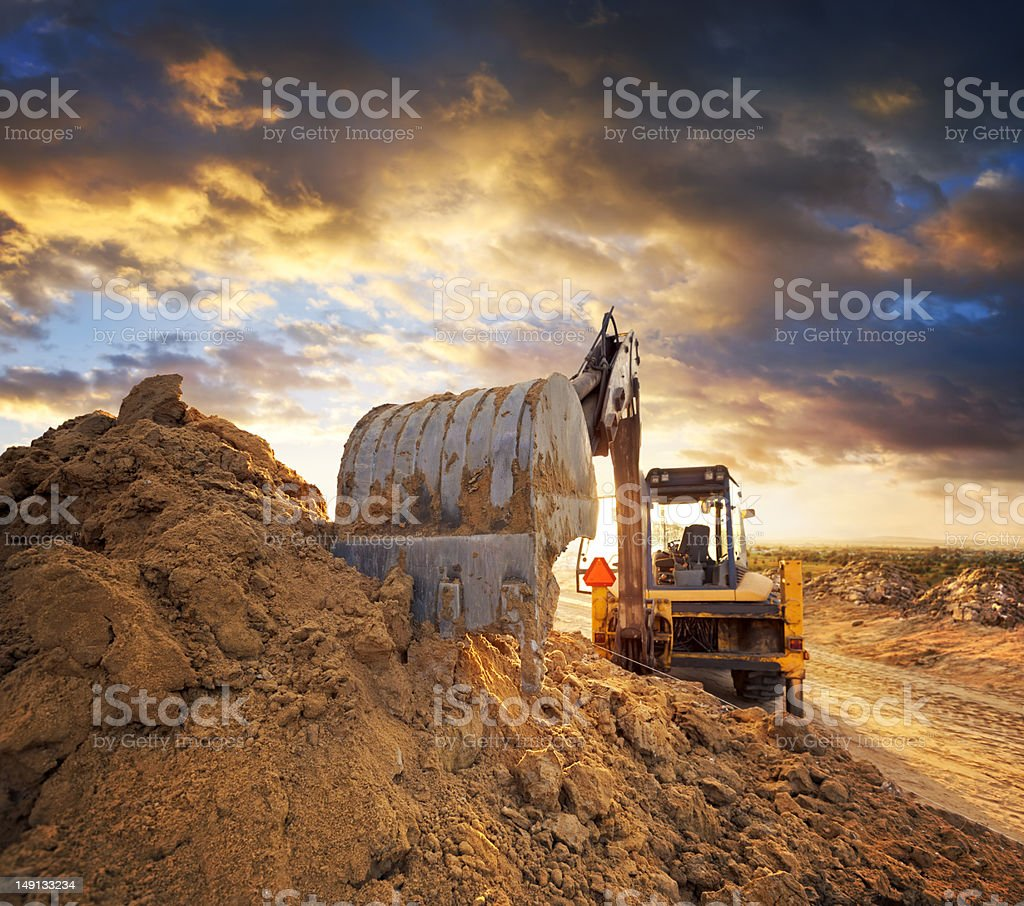 Excavator on the construction site of the road against the setting sun stock photo