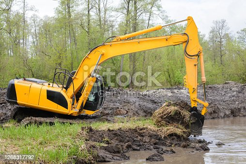 Excavator picks up big amount of soil for construction irrigation system canal in countryside for watering