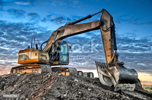 Excavator on construction site, and the sunrise in background. HDR effect.