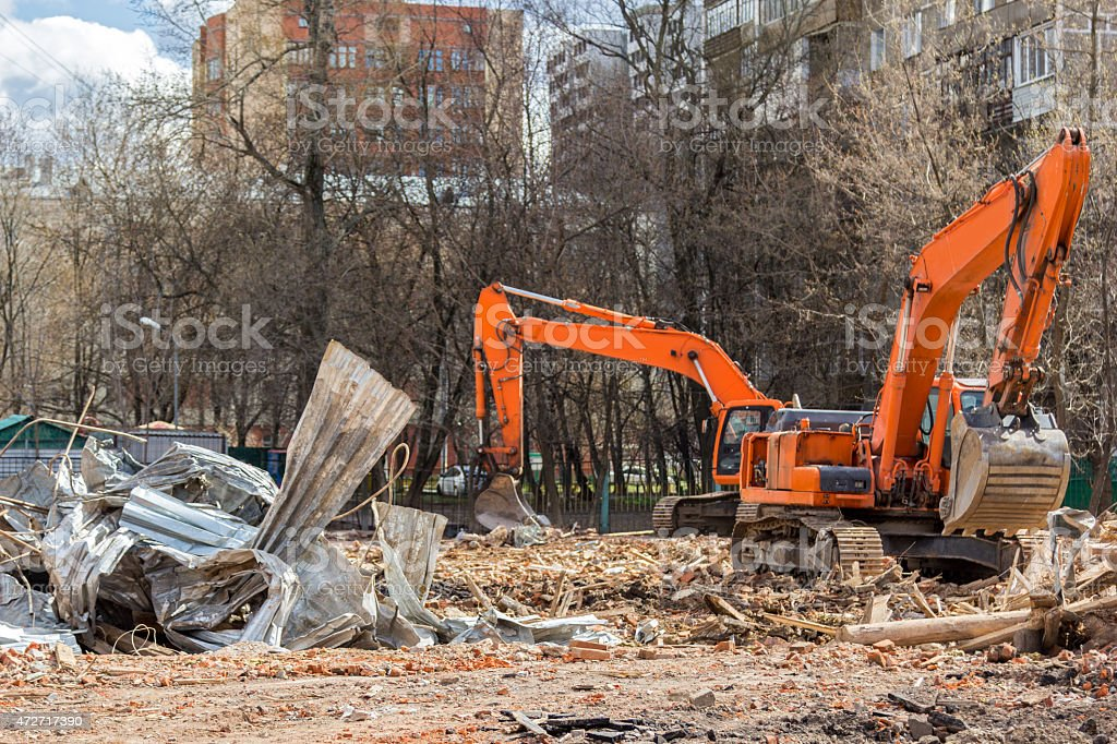 excavator removes construction waste after building demolition f stock photo