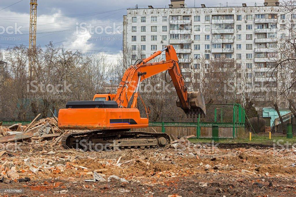 excavator removes construction waste after building demolition stock photo