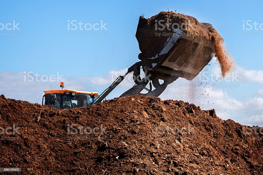 Excavator shovel working on a large heap of, organic fertilizer stock photo