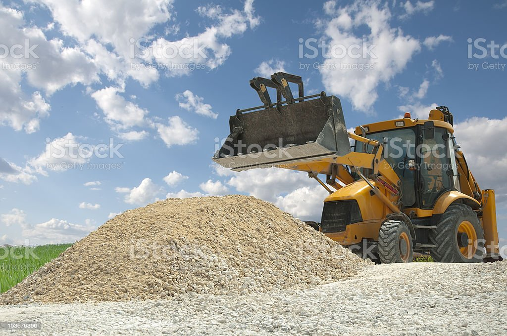 Excavator to a pile of rubble royalty-free stock photo