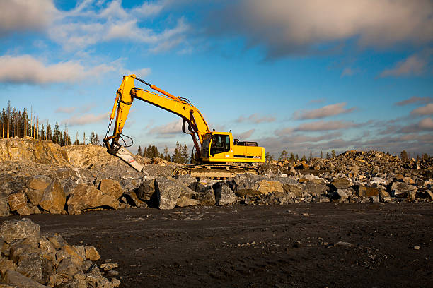 Excavator with Hydraulic Hammer Working in Gravel Pit stock photo