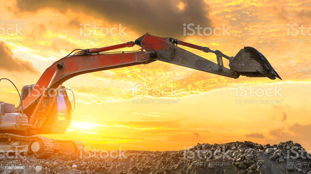 Excavator work on construction site at sunset,industrial background