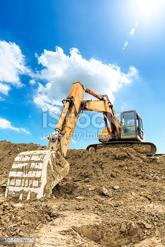 Excavator working at building site on sunny day,industrial background