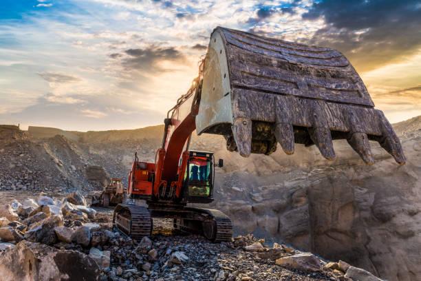 graafmachine werkzaam bij mining site - steengroeve stockfoto's en -beelden