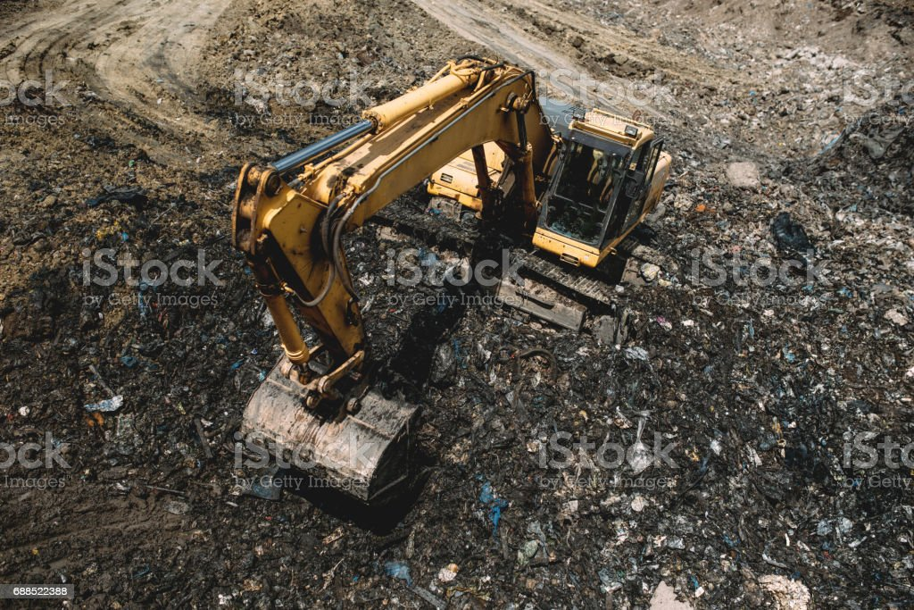 Excavator working in dump site. Industrial details of machinery working and digging stock photo