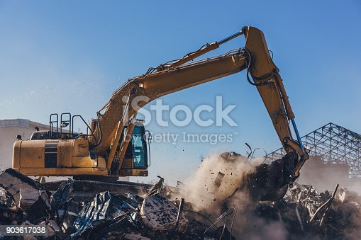 Excavator machinery working on a big demolition site of old building