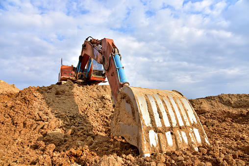 Excavator working on earthmoving at open pit mining. Backhoe digs gravel in quarry. Construction machinery for excavation, loading, lifting and hauling of cargo on job sites