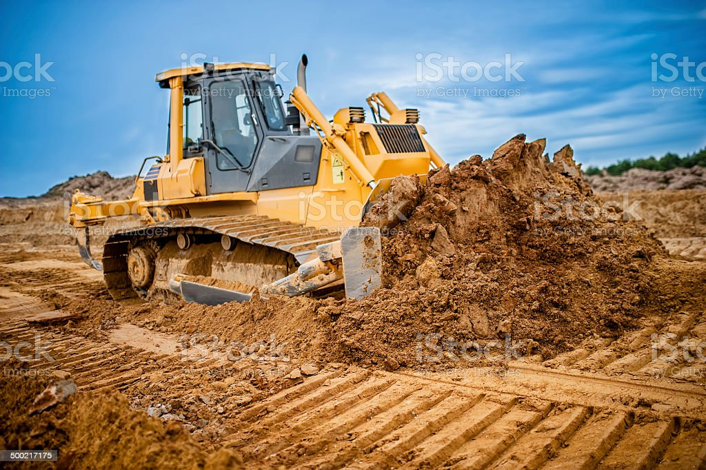 Excavator working with earth and sand in sandpit in highway stock photo