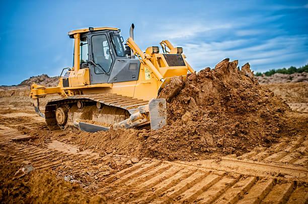 excavator working with earth and sand in sandpit in highway - graven stockfoto's en -beelden