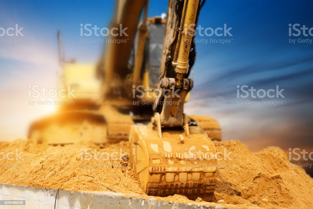Excavators machine in construction site on sunset background stock photo
